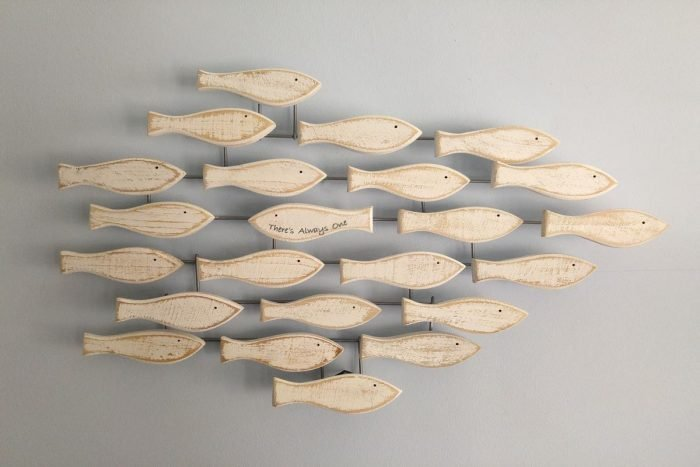 white wooden shoal of fish wall art with one fish swimming other way