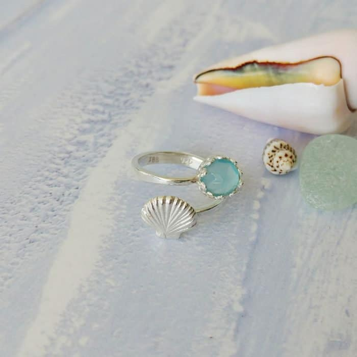 adjustable sterling silver ring with a shell design and blue chalcedony gemstone set inside a crown setting