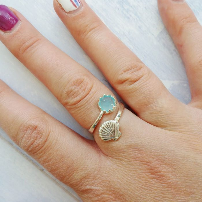 adjustable sterling silver ring with a shell design and blue chalcedony gemstone set inside a crown setting modelled on a hand