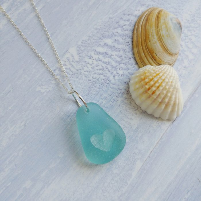 Light blue seaglass pendant hanging on a sterling silver chain. The seaglass has a carved heart in the centre