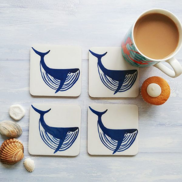 set of four white coasters whith blue sperm whale