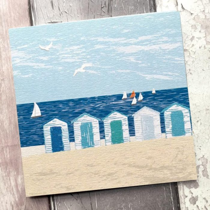 Greetings card featuring colourful beach huts golden sand and sparkling blue sea