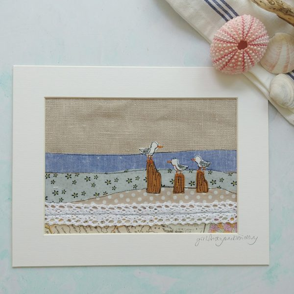 embroidered textile layered fabric wall art depicting the beach on linen background. Tiny felt seagulls on their wooden breaker perches are freehand embroidered to add detail