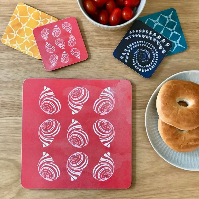 beautiful bright coral red coastal shell placemats with hand drawn shells contrasted with a gorgeous watercolour background