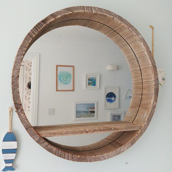 large wooden porthole mirror with shelf